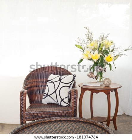 Outdoor chair in flower setting in front of white curtain - stock photo