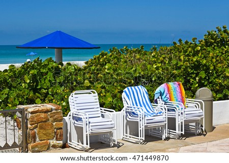 Outdoor Chairs stacked on patio with a view of the Ocean and White Sandy Beach of Anna Maria Island, Florida in the background