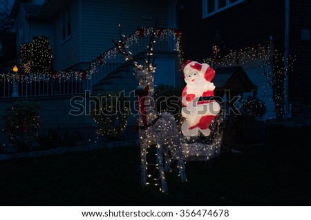 Outdoor Christmas decoration - electrical garlands and figurines in residential area - stock photo
