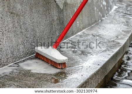 Outdoor cleaning with red brush.