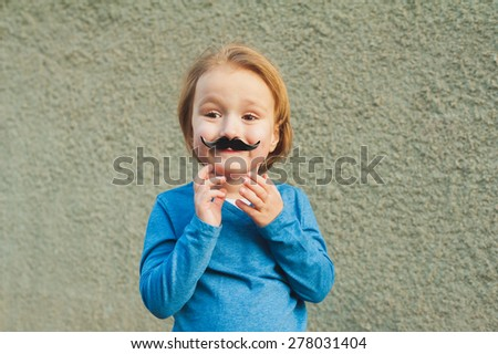 Outdoor close up portrait of a cute little boy with fake italian mustache - stock photo