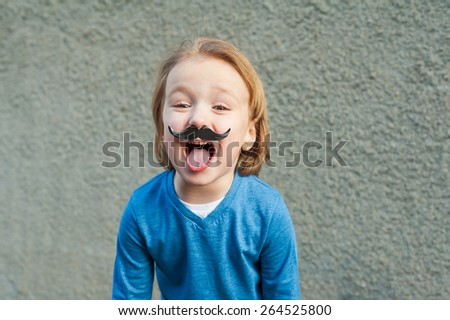 Outdoor close up portrait of a cute little boy with fake moustache, showing a tongue. Little einstein style - stock photo