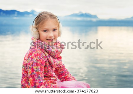 Outdoor close up portrait of adorable little kid girl of 8 years old resting by the lake Geneva on a nice winter day, wearing colorful pink pullover and warm earmuffs