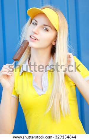 Outdoor closeup colorful portrait of young pretty blonde woman eating ice cream. Soft focus