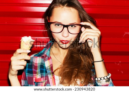 Outdoor closeup fashion portrait of pretty young sensual hipster girl with red lips and ice-cream in her hand posing in the night  - stock photo
