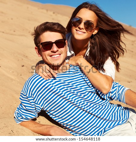 Outdoor closeup fashion portrait of young beautiful stylish couple in summer on the beach. Fun and sun together. - stock photo