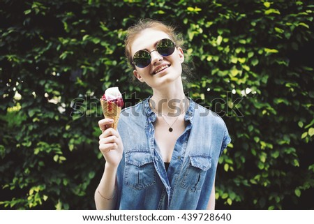 Outdoor closeup fashion portrait of young hipster crazy girl eating ice cream in summer hot weather in round mirror sunglasses have fun and good mood. Toned style instagram filters - stock photo