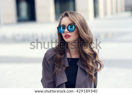 Outdoor closeup fashion style portrait of young pretty stylish girl with long curly hair wearing sunglasses - stock photo