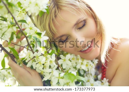 outdoor closeup portrait of a beautiful blonde woman among blossom apple trees