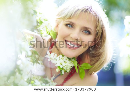 outdoor closeup portrait of a beautiful blonde woman among blossom apple trees - stock photo