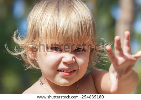 Outdoor closeup portrait of cute angry Caucasian blond baby girl - stock photo