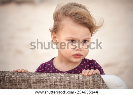 Outdoor closeup portrait of cute serious Caucasian blond baby girl  - stock photo