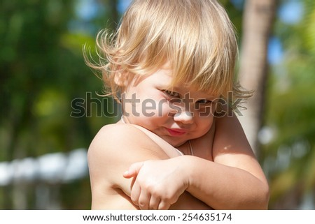 Outdoor closeup portrait of cute shy Caucasian blond baby girl - stock photo