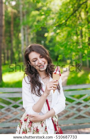Outdoor closeup portrait of girl eating ice cream in summer