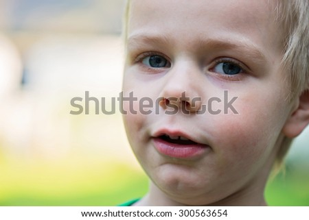 Outdoor closeup portrait of happy kid face. Shallow depth of field. Focus on the left eye - stock photo