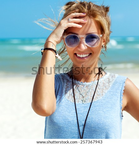 Outdoor closeup portrait of pretty young blonde smiling woman in blue sunglasses having fun on the beach