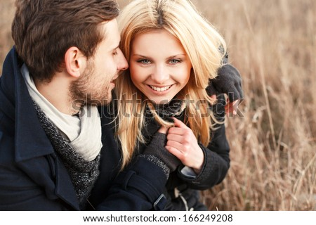 Outdoor closeup portrait of young pretty fashion couple. Smiling happy blonde woman with her handsome boyfriend posing in cold weather, smiling and having sensual fun - stock photo