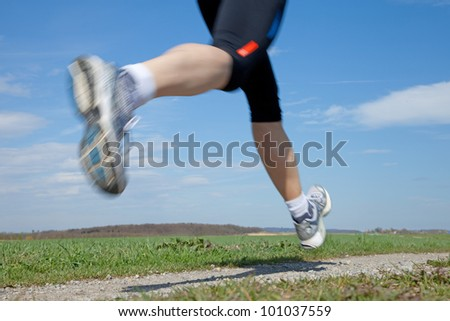 Outdoor closeup shot of a male runner running at a fast pace