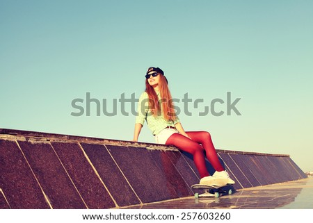 Outdoor closeup summer portrait of pretty girl posing in urban youth style. Fashion lifestyle. Beautiful young woman having fun together with skate board. Photo toned style instagram filters - stock photo
