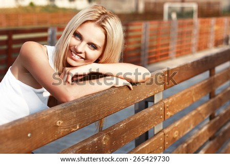 Outdoor closeup summer portrait of young pretty blonde smiling woman  - stock photo
