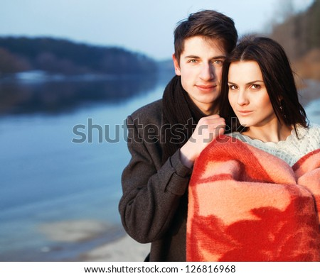 Outdoor cold spring portrait of young attractive couple in love. Boy and girl standing near water in warm clothes. - stock photo