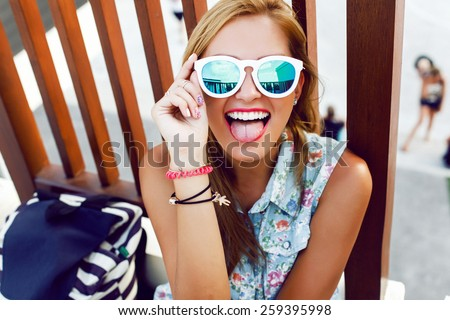 Outdoor colorful summer closeup of young pretty blonde happy smiling girl showing tongue and having fun on the street  - stock photo