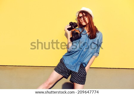 Outdoor colorful summer portrait of pretty smiling happy sensual hipster style woman going crazy and shocked and saying hello on yellow background with photo camera retro style vintage  - stock photo