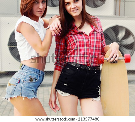 Outdoor colorful vintage portrait of two pretty fashion girls friends dressed in sexy shorts sensual photo with longboard urban style