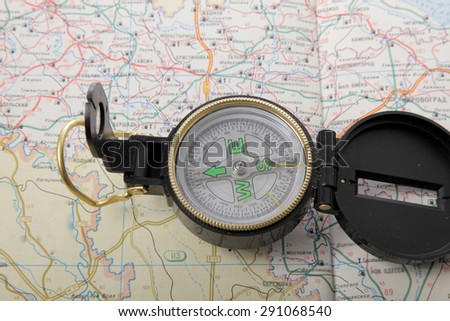 Outdoor compass with black lid it is over a topographic map