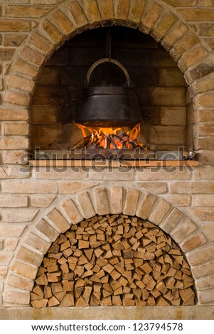 Outdoor cooking in a barbecue fireplace, kettle of boiling fish stew - stock photo