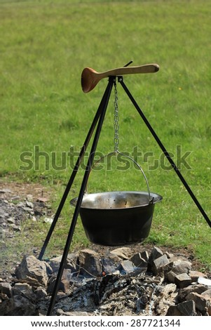 Outdoor cooking in cauldron