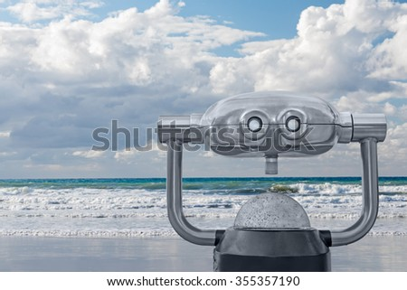 Outdoor daytime viewing telescope looking at foamy ocean waves, cloudy sky, and horizon. Blurred background. Gray metal swivel scope with two eyepieces and focusing knob. Copy space.  - stock photo