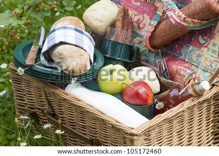 outdoor dining : picnic basket on lawn with fresh olive-baguette, milk, apple and sausages, bread and pieplant juice. - stock photo