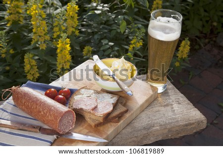 outdoor dining :  ( picnic ) with salami, bread,butter,tomatoes and a wheat beer.
