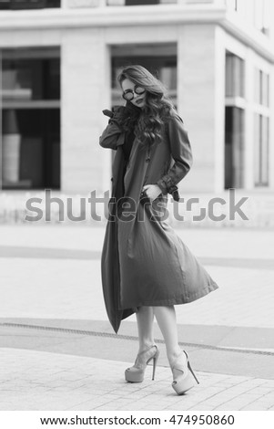 Outdoor dynamic fashion portrait of young beautiful stylish woman in black dress, grey coat and sunglasses walking on a windy day against city background
