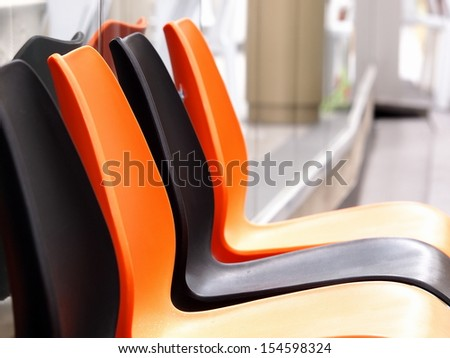 outdoor empty colorful plastic chairs setting in groups  - stock photo