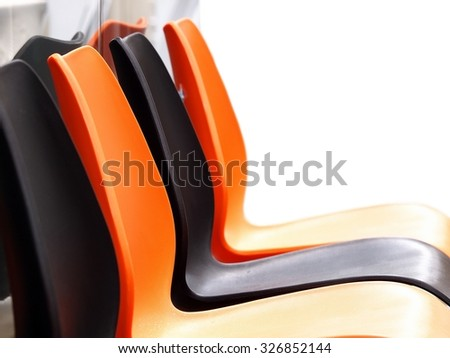 outdoor empty colorful plastic chairs setting in groups in front of glass wall with reflections under bright natural sunlight, die-cut isolated on white background - stock photo