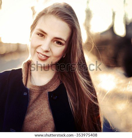 Outdoor evening sensual closeup portrait of pretty young smiling sensual girl having fun on the street