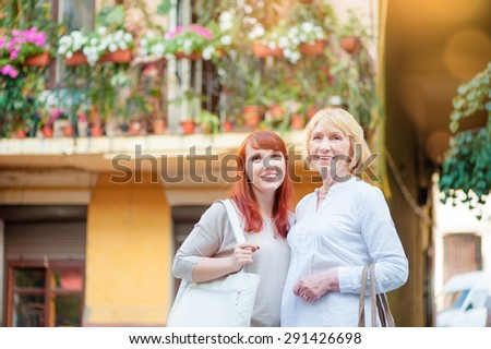 Outdoor family portrait of  Middle aged Mother and her Adult Daughter  walking on city street. - stock photo