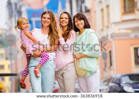 Outdoor family portrait - three women with little girl. - stock photo