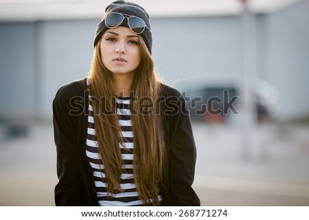 Outdoor fashion closeup portrait of nice pretty young hipster woman posing at sunset walks along the streets of the city. - stock photo