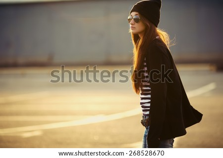 Outdoor fashion closeup portrait of nice pretty young hipster woman posing in sunglasses at sunset walks along the streets of the city. - stock photo