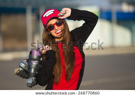 Outdoor fashion closeup portrait of nice pretty young hipster woman posing in sunglasses at sunset walks along with roller skate the streets of the city. - stock photo