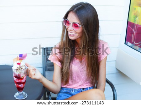 Outdoor fashion closeup portrait of nice pretty young hipster woman posing with ice-cream smiling going crazy and showing long tongue