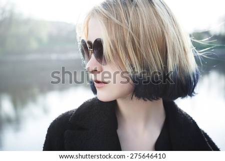 Outdoor fashion closeup portrait of young pretty woman in summer sunny day on street - stock photo