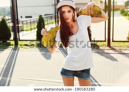 Outdoor fashion closeup summer portrait of pretty young woman posing in urban youth style in town. Summer evening sunlight - stock photo