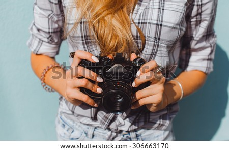 Outdoor fashion details, sexy woman wearing elegant beige clothes and holding vintage retro camera on her hands,stylish classic accessorizes,toned colors.Photographer.polaroid  - stock photo
