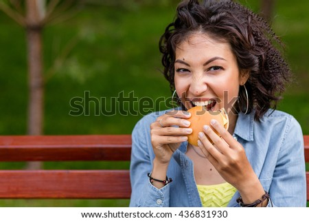 Outdoor fashion funny hipster style portrait of beautiful brunette mulatto woman eating tasty hamburger on the street - stock photo