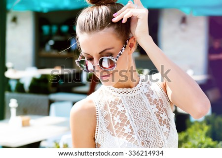 Outdoor fashion image of stylish young lady,fashionable.Lifestyle portrait of stunning hipster girl, wearing elegant glamour jacket dress and vintage sunglasses, toned warm colors, positive mood - stock photo