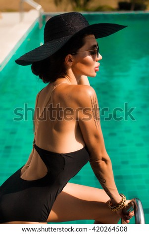 Outdoor fashion image of young woman in black swimsuit,summer outfit ,rest her time on hotel,black hat ,Elegant sexy woman,sun-tanned slim and shapely body,posing near swimming pool,golden bracelet - stock photo